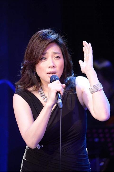 ライブで熱唱している黒いワンピースを着ている藤吉久美子の画像